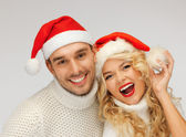 Family couple in sweaters and santa's hats — Stockfoto