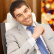 Young businessman sitting in chair - Foto Stock