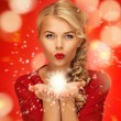 Woman blowing magic on the palms of her hands — Stockfoto