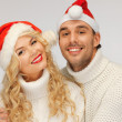 Family couple in sweaters and santa's hats — Stock Photo #16077077