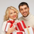 Family couple in a sweaters with gift boxes — Stock fotografie