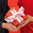 Stock Photo: Man and woman's hands with gift box