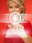Woman in red dress pressing virtual button — Stock Photo