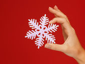 Woman's hands holding a snowflake — Stockfoto