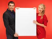 Couple holding big blank board — Stock Photo