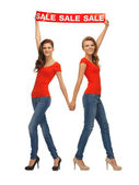 Two teenage girls with sale sign — Stock Photo