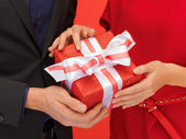 Man and woman's hands with gift box — Stock Photo