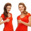 Wo teenage girls in red t-shirts showing thumbs up — Stock Photo