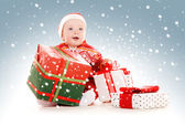 Santa helper baby with christmas gifts — Stock fotografie