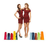Teenage girls in red dresses with shopping bags — Stock Photo