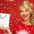 Lovely woman in red dress with shopping bag — Stock Photo #16969079