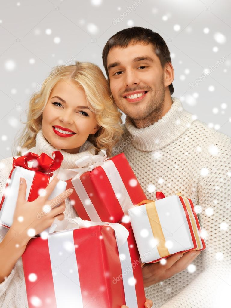 Picture of family couple in a sweaters with gift boxes — Stock Photo #16969107