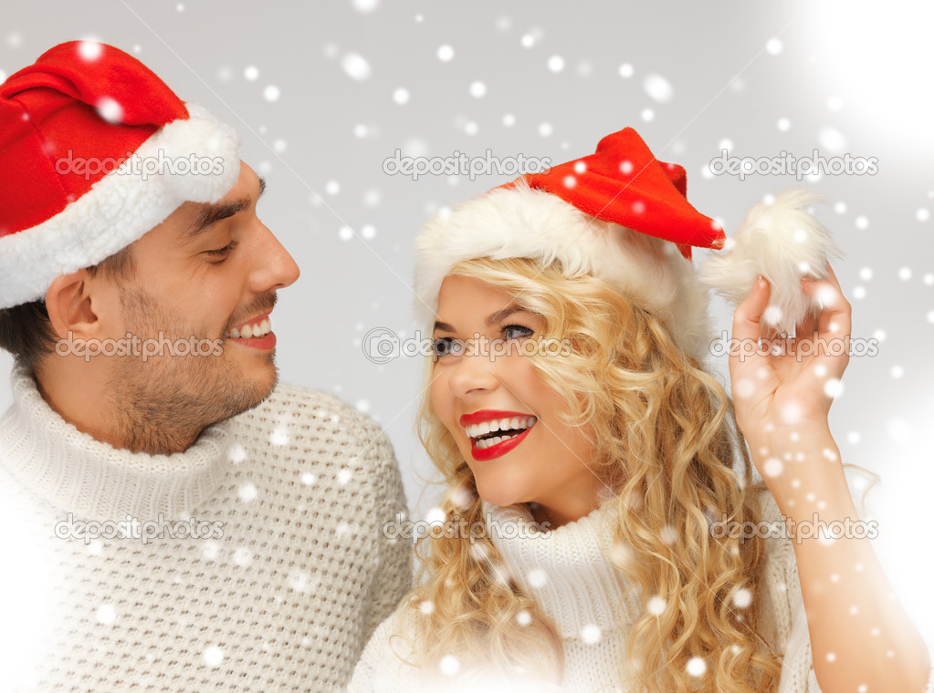 Picture of family couple in sweaters and santa's hats — Stock Photo #16969121