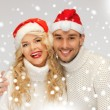 Stok fotoğraf: Family couple in sweaters and santa's hats