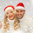 Foto de Stock  : Family couple in sweaters and santa's hats