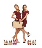 Two teenage girls in red dresses with bag — Stock Photo