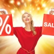 Stock Photo: Beautiful womin red dress with shopping bag