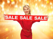 Lovely woman in red dress with sale sign — Stock Photo