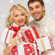 Family couple in a sweaters with gift boxes — Stock Photo #17166823