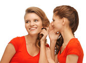 Two talking teenage girls in red t-shirts — Stock Photo