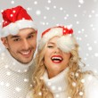 Family couple in sweaters and santa's hats - Stock Photo