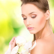 Beautiful woman with orchid flower — Stock Photo #17423363