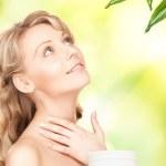 Beautiful woman with moisturizing creme — Stock Photo #17423481