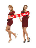 Teenage girsl in red dresses with sale sign — Стоковое фото