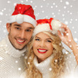 Family couple in sweaters and santa's hats — Stock Photo #17508555