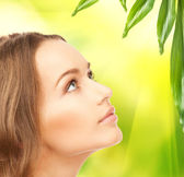 Beautiful woman with green leaves — Stock Photo