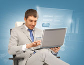Young businessman sitting in chair with laptop — Foto Stock