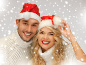 Family couple in sweaters and santa's hats — Stock fotografie