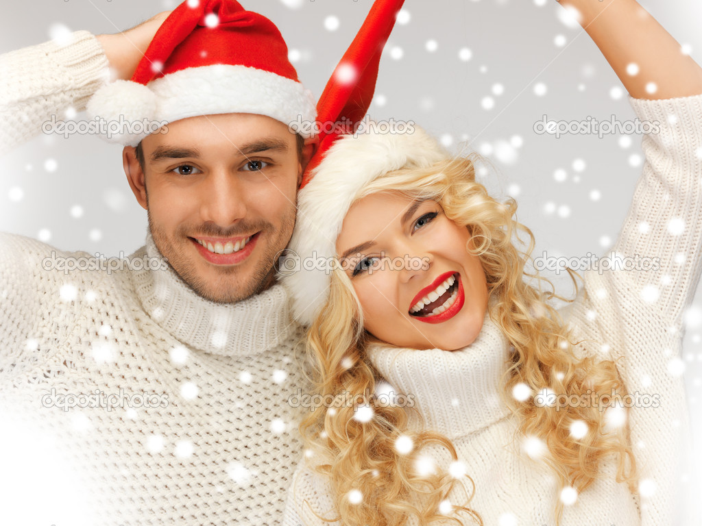Picture of family couple in sweaters and santa's hats — Stock Photo #17508887