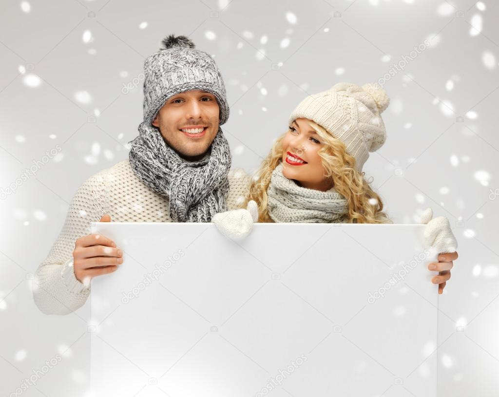 Picture of family couple in a winter clothes holding blank board  Stock Photo #17508973