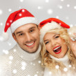 Family couple in sweaters and santa's hats - Foto Stock