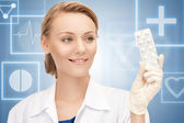 Attractive female doctor with pills — Stock Photo