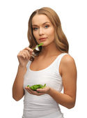 Woman with spinach leaves on palms — Stock Photo