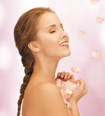 Beautiful woman with rose petals — Stock Photo