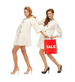 Teenage girls in white coats with shopping bags — Stock Photo