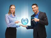 Man and woman showing earth globe on the palms — Stock Photo