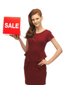 Teenage girl in red dress with sale sign — Stock Photo