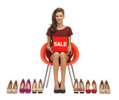 Teenage girl in red dress with shoes and sale sign — Stock Photo