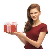Teenage girl in red dress with gift box — Stock Photo
