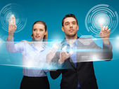 Man and woman working with virtual touch screens — Stock Photo