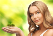 Woman with green grass on palms — Stock Photo