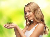 Femme avec une herbe verte sur la paume — Photo