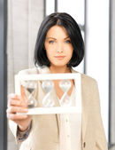 Pensive businesswoman with sand glass — Stock Photo
