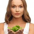 Woman with spinach leaves on palms — Stock Photo #18474015