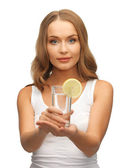 Woman with lemon slice on glass of water — Stock Photo