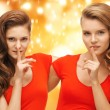 Stock Photo: Two teenage girls showing hush gesture